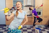 Modern kitchen - woman pretend to sing song with ladle and smiling young man cleaning the floor at home and play like guitar with  mop