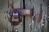 stock photo of hasp  - Corroded padlock and hasp secures weathered wooden door - JPG
