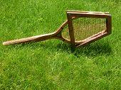 Vintage tennis racket on grass court