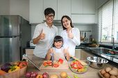 Asian Family With Father, Mother And Daughter Shredded Vegetable Salad And Thump Up While The Family poster