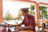 A Woman Works Remotely. Freelancer Works On A Journey. Girl Sitting At A Laptop. Distance Learning.  poster