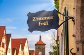 Zimmer frei (Rooms available) sign at a guesthouse or hotel with Half-timbered houses in background. poster