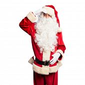 Middle age handsome man wearing Santa Claus costume and beard standing worried and stressed about a  poster