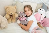 Carefree Childhood. Relaxing Before Sleep. Girl Enjoy Evening Time With Toys. Kid Lay Bed With Toys  poster