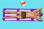 Top View Of Young Caucasian Male Models Resting On Beach Resort On Purple Mat And Blue Background. M poster