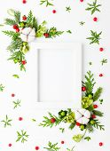 Christmas composition  with photo frame, cotton flower, branches of spruce and holly with red berrie poster