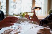 Wine Glasses With White Wine In A Restaurant. People Clink Glasses Of Wine In A Restaurant Celebrati poster