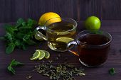Cups Of Green And Black Tea With Lemon And Cinnamon On Wooden Background And Leaves Of Green Mint. H poster