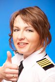 Beautiful airline pilot wearing uniform with epauletes showing thumb up gesture of approval, standing on blue background.