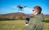A Man Pilots A Drone In Nature By Controlling It From A Remote Control. poster