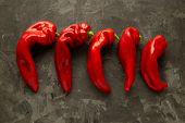 Five Fresh Ugly Red Sweet Peppers Lie On A Dark Background. Place For Text. Ugly Food. poster