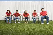 Familia de raza mixta, sentados en sillas de jardín