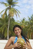 South American woman drinking from coconut