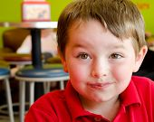 Young boy's face covered with chocolate after eating frozen yogurt at frozen yogurt or ice cream sho