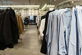 Modern Fashion Store. Buyers Choose Clothes. Shirts, Hoodies, Blouses And Half-sweaters, A Sweater O poster