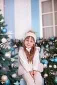 Merry Christmas, Happy Holidays! New Year 2020. Little Girl Sits Near Christmas Tree On Porch Of Hou poster