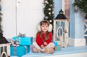 Merry Christmas, Happy Holidays! New Year 2020. Little Girl Is Sitting In Red Sweater With Gift On P poster