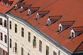 Top View Of Old Building With Red Roof And Windows On The Roof. European City, View From Elevation P poster