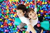 pic of playground  - Little smiling boy playing lying in colorful balls park playground - JPG