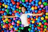 stock photo of indoor games  - Little smiling boy playing lying in colorful balls park playground - JPG