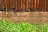 Background Of Rusty Corrugated Iron And Brick Wall In Front Of Grass