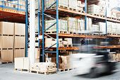 picture of forklift driver  - warehouse worker driver in uniform loading cardboxes by forklift stacker loader - JPG