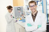 Portrait of young smiling male researcher in front of female researcher carrying out scientific test
