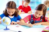 stock photo of schoolboys  - Portrait of lovely girls drawing at workplace with schoolboys on background - JPG