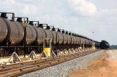 stock photo of railroad car  - Long lines of railroad oil tanker cars stretch off into the distance down the train tracks waiting to be unloaded - JPG