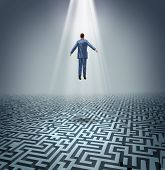 stock photo of levitation  - Powerful solutions with a businessman levitating above a maze or labyrinth as a business concept of leadership and conquering challenges and obstacles with a man rising above to find the answers - JPG