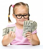 Cute little girl is counting dollars, isolated over white