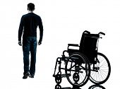 foto of wheelchair  - one man walking away from wheelchair in silhouette studio on white background - JPG