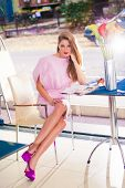 elegant young woman in pink dress and high heel shoes sit in cafe with cake and magazine on table fu