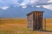 stock photo of outhouse  - Outhouse in Mormon Row with Teton Range in background - JPG