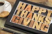 Happy Thanksgiving in letterpress wood type on digital tablet computer with stylus pen, coffee cup a
