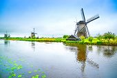 stock photo of windmills  - Windmills and water canal in Kinderdijk Holland or Netherlands - JPG