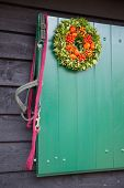stock photo of reining  - Several horse reins hanging at green wooden stable door outside - JPG