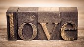 The word LOVE written with vintage printing blocks over old wood background