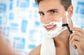 young man shaving his beard with razor reflected on the bathroom's mirror