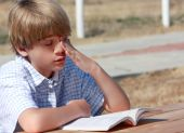 stock photo of dyslexia  - Very bored teenager at an outside table trying to read - JPG