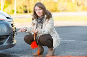 image of towing  - Beautiful woman assembling towing hook to a broken car and holding tow rope in the other hand - JPG