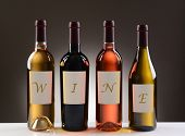 Four Wine Bottles with their labels spelling out the word WINE, on a light to dark gray background.