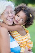 Grandmother hugs her hispanic granddaughter and laughs (with a diffused green grass background)