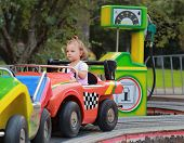 Driving Car Baby Girl On Road In Amusement Park On Weekend