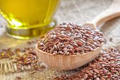 stock photo of flax seed oil  - Flax seeds in a wooden spoon and linseed oil - JPG