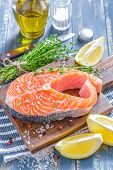 stock photo of redfish  - Raw salmon with lemon on a board - JPG