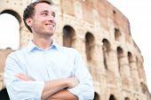 Young casual business man portrait by Colosseum, Rome, Italy. Proud confident happy smiling cross-ar