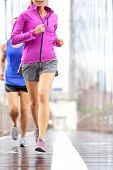 Running people - couple jogging and training for marathon. Runners in rain outside. Asian woman and
