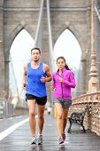 Running couple jogging training for New York marathon. Runners in rain outside. Asian woman and Caucasian man runner and fitness sport models jogging on Brooklyn Bridge, New York City, USA