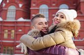 Happy man and woman embrace near red building at winter day.